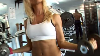 Sporty slut Sandy warms up in a gym and gets horny